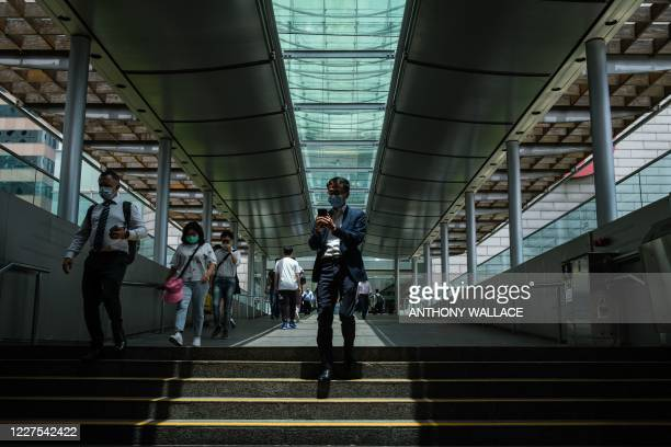 Workers and pedestrians walk on a footbridge in the Central district of Hong Kong on July 16, 2020. - Beijing's tough new security law and President...