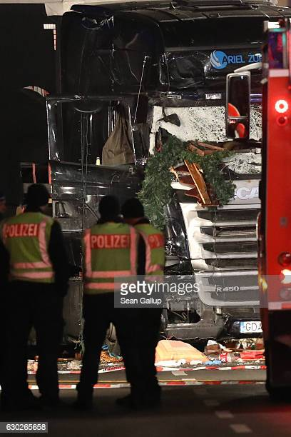 Workers and security inspect the damaged lorry truck after it was ploughed through a Christmas market on December 19 2016 in Berlin Germany Several...