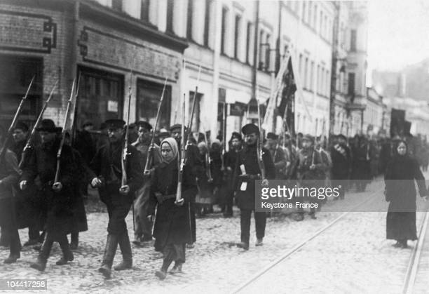 Workers and soldiers who fled the front along with women parading in arms in the streets of Petrograd after the first Russian Revolution of February...