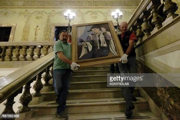 Workers and technicians prepares the exhibition Harlequin at mirror by Pablo Picasso at Palazzo Zevallos/Gallerie d'Italia