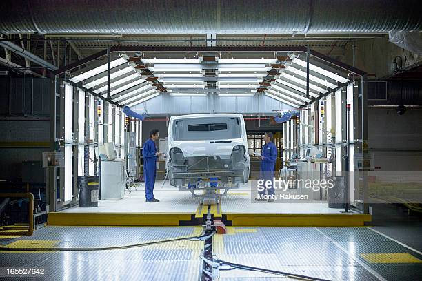 Workers and vehicle in inspection station in car factory