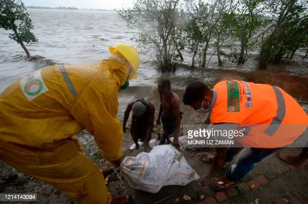 Workers and villagers reinforce an embankment with sacks of soil ahead of the expected landfall of cyclone Amphan in Dacope on May 20 2020 Several...