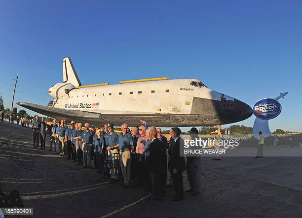 Workers and visitors watch as the US Space Shuttle Atlantis moves on November 2, 2012 to the Visitors Center at Kennedy Space Center in Cape...