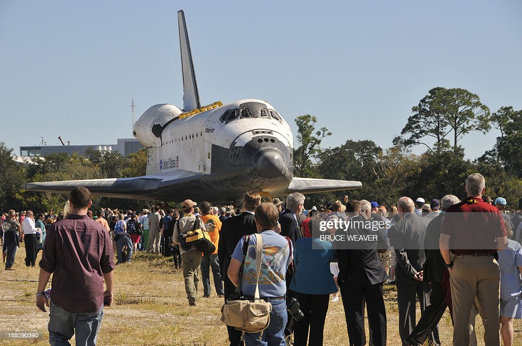 Workers and visitors watch the US Space Shuttle Atlantis moves on November 2, 2012 to the Visitors Center at Kennedy Space Center in Cape Canaveral, Florida, for permanent display. The spacecraft traveled 125,935,769 miles (202,673,974 kms) during 33 spaceflights, including 12 missions to the International Space Station. Its final mission, STS-135, closed out the Space Shuttle Program era with a landing on July 21, 2011. AFP PHOTO/Bruce Weaver