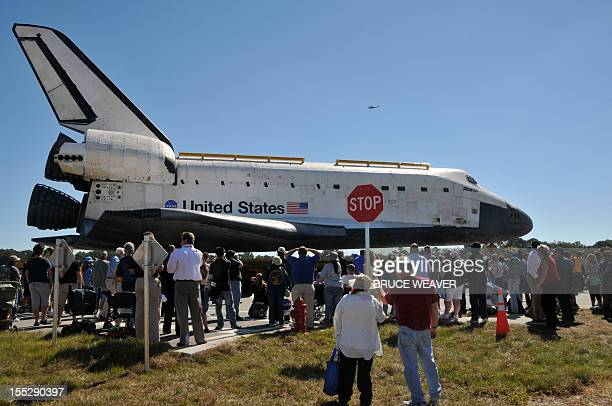 Workers and visitors watch the US Space Shuttle Atlantis moves on November 2, 2012 to the Visitors Center at Kennedy Space Center in Cape Canaveral,...