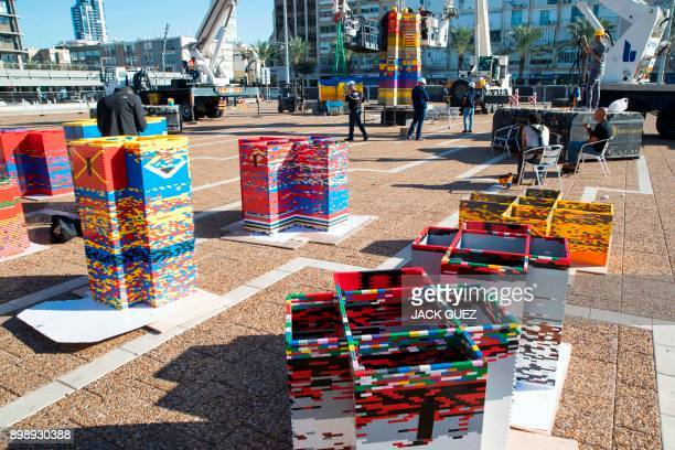 Workers and volunteers help assemble bricks during the construction of a LEGO tower in Tel Aviv's Rabin Square on December 26 as the city attempts to...