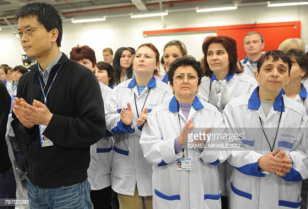 Workers applaud an inaugural speech at the Finnish cellphone maker Nokia factory in the Romanian village Jucu 500 kms northwest of Bucharest on...