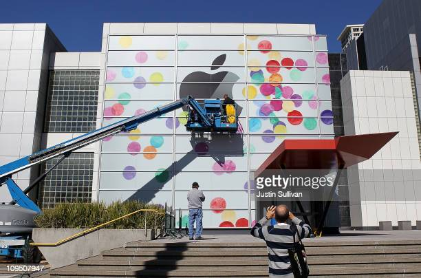 Workers apply the Apple logo the outside of the Yerba Buena Center for the Arts on February 28, 2011 in San Francisco, California. Apple is preparing...