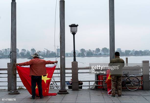 Workers are arranging the Chinese national flags on a square beside the Yalu River, where tourists and citizens can overlook North Korea. Dandong is...