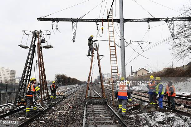 Workers are at work on December 21 2009 after an IledeFrance Paris regional train Transilien derailed after a car swerved on ice and hit a bridge...