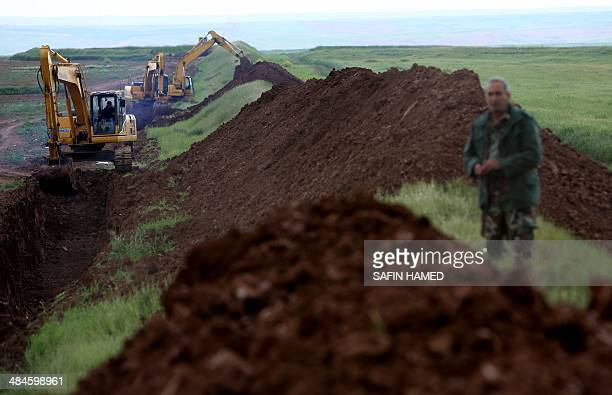 Workers are digging a trench on the northern Iraqi border with Syria to prevent people from crossing over into Iraq's autonomous Kurdistan region on...