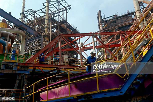 Workers are dwarfed by machinery at a Potash recovery plant at the Dead Sea Works complex on the shores of the Dead Sea September 2 2004 in Sodom...