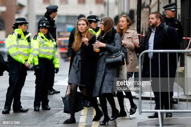 Workers are evacuated from offices on a street adjoining The Strand in central London on January 23 2018 after a gas leak closed The Strand and...
