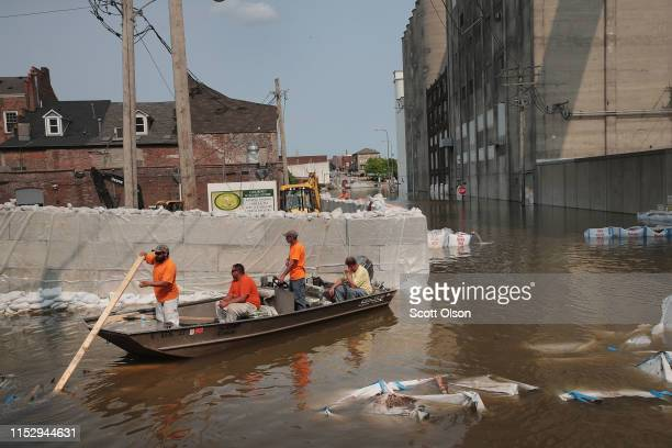 Workers are ferried through floodwater from the Mississippi River across Highway 100 to their jobs at Ardent Mills on May 31 2019 in Alton Illinois...