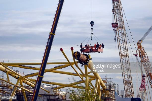 Workers are lowered on a platform amongst the giant steel structures for offshore wind power developments which dominate the Methil yard of...