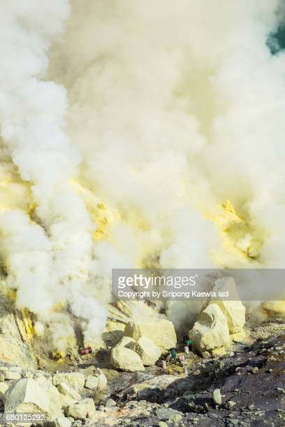 workers are mining the sulfur in the middle of sulfuric acid smoke at kawah ijen, indonesia. - acid warning stock photos and pictures