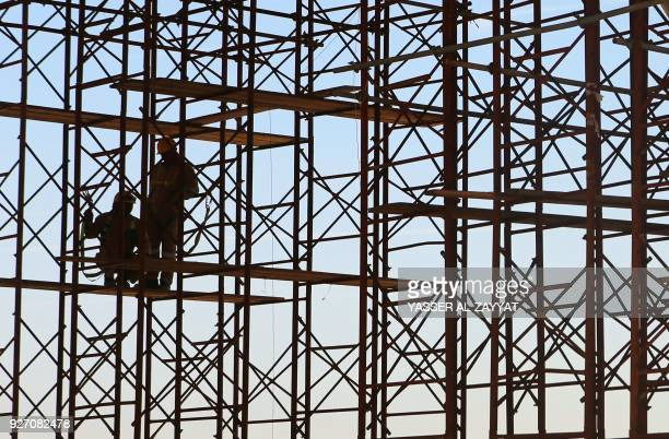 Workers are pictured on the site of the Jaber AlAhmad Causeway in Kuwait City on March 4 2018 The Causeway is considered one of the longest in the...