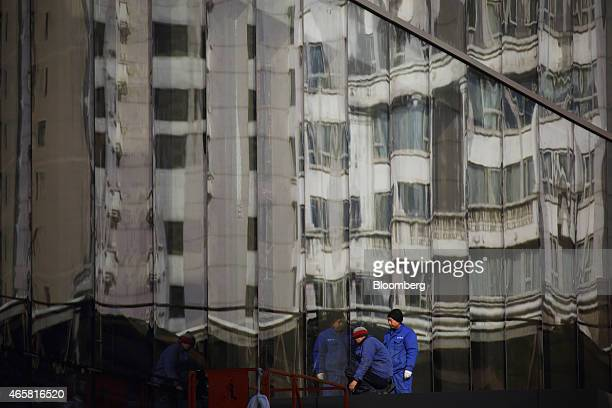 Workers are reflected in windows of a residential building under construction in Beijing China on Tuesday March 10 2015 China set the lowest economic...