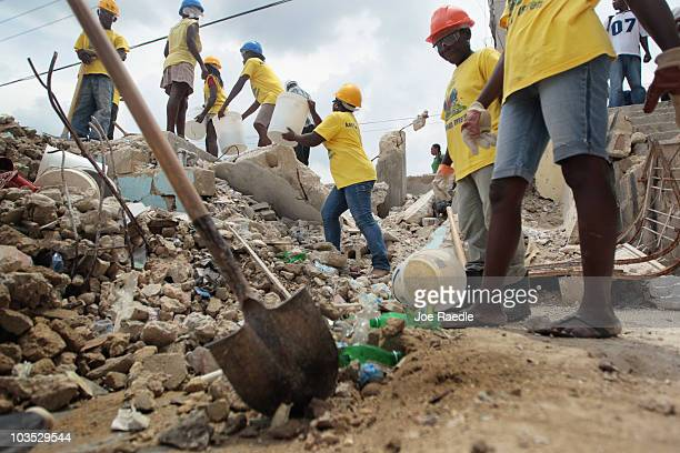 Workers are seen as they form a bucket brigade to clear the rubble of a collapsed building on August 21, 2010 in Port-au-Prince, Haiti. After the...