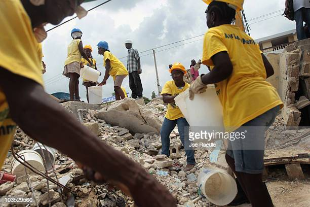 Workers are seen as they form a bucket brigade to clear the rubble of a collapsed building on August 21 2010 in PortauPrince Haiti After the official...