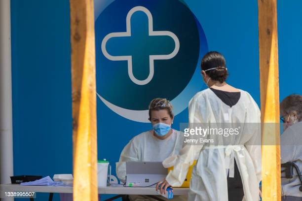 Workers are seen at a COVID-19 vaccination clinic at a Pharmacy on September 08, 2021 in Narromine, Australia. New freedoms have been announced for...