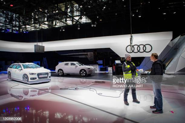Workers are seen at the stand of German carmaker Audi on February 28, 2020 at the Geneva International Motor Show which has been cancelled after...