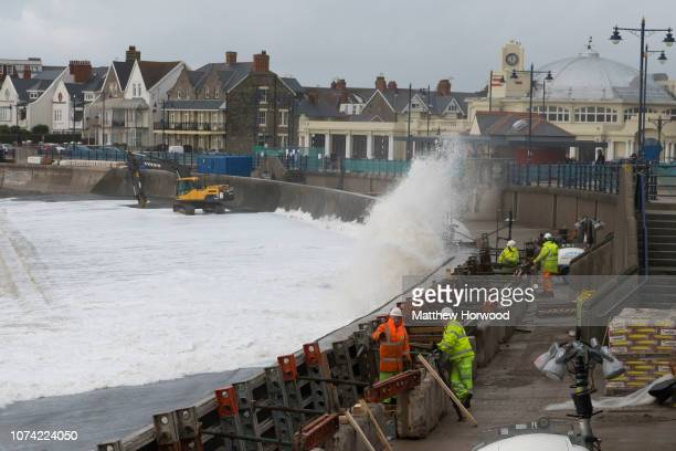 Workers are seen at work on a new coastal seawall on November 29, 2018 in Porthcawl, Wales. The Met Office have issued a number of weather warnings...