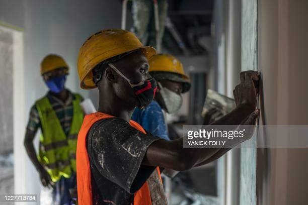 Workers are seen finishing the work at the innovative building at the Sèmè-One building, an incubator for Beninese start-ups, in Cotonou on July 8,...