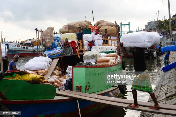 Workers are seen loading commodities in a cargo boat in the Buriganga river. After months of the ongoing pandemic, Dhaka is getting back to its...