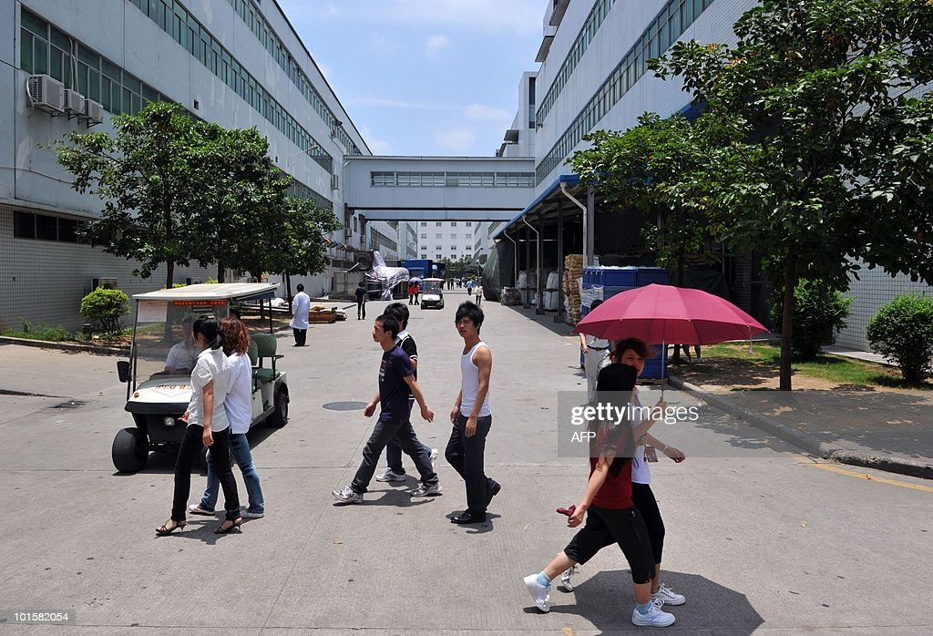 Workers are seen next to factory building at the giant Foxconn plant in Shenzen on May 26, 2010. The Taiwanese boss of Apple manufacturer Foxconn headed to a sprawling factory in southern China where a spate of worker suicides have stoked anger about labour conditions. Terry Gou, the chairman of Foxconn's parent company Hon Hai Precision, flew into the booming city of Shenzhen aboard his private jet with travelling Taiwanese reporters, urging the media to see the factory for themselves.