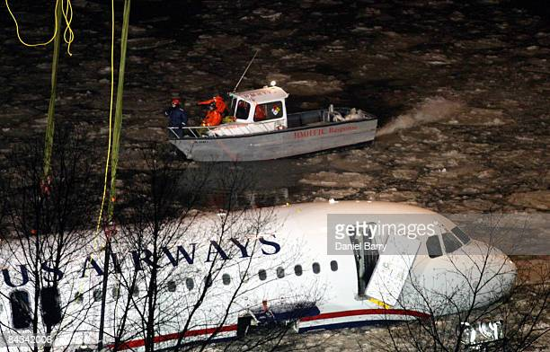 Workers are seen on a boat as the US Airways Airbus A320 is lifted from the Hudson River January 17 2009 in New York City US Airways Flight 1549...
