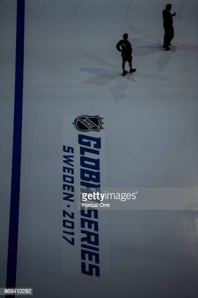 Workers are seen on the ice passing the Global Series logo during the rink build out ahead of the SAP NHL Global Series between Ottawa Senators and...