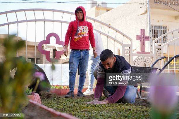 Workers are seen planting grass at the Grand Immaculate Church garden days before the Pope's historic visit to Iraq. The town of Qaraqosh, 30...