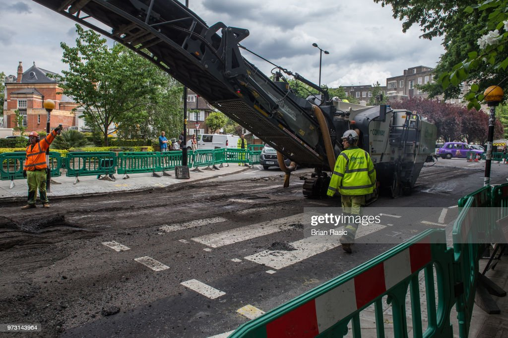 Workers are seen re tarmacing the iconic Abbey Road Zebra Crossing on June 13, 2018 in London, England.