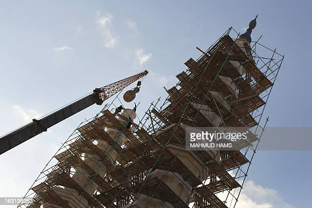 Workers are seen standing on scaffolding surrounding a the minaret of a mosque under construction along the seafront in Gaza City on March 5 2013 A...