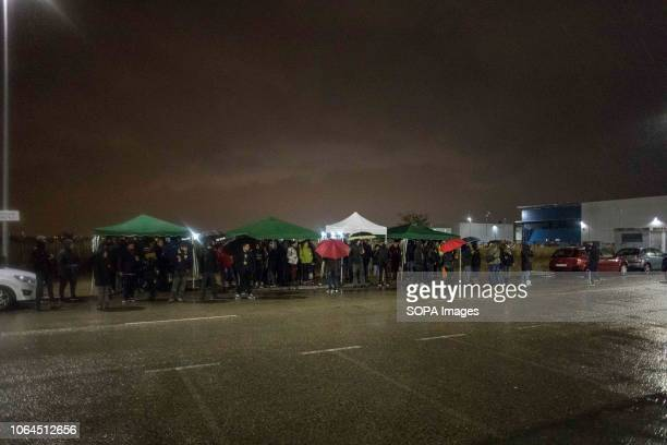 Workers are seen taking cover from the rain at the entrance of the Amazon warehouse during the strike The workers of the largest Amazon warehouse in...