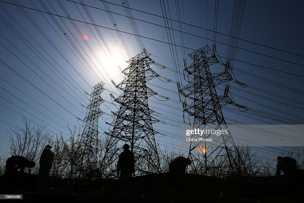Workers are shown near electric transmission pole towers April 8, 2007 in Beijing, China. China generated 16.6 percent more energy in the first two months of 2007 over the same period last year, according to data released by the China Electricity Council (CEC). The CEC noted that energy use for all of 2006 increased 13.99 percent over 2005.
