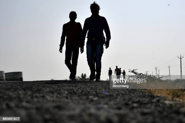 Workers are silhouetted as they walk along a road running through the project site for a 920squarekilometer industrial area located on the...