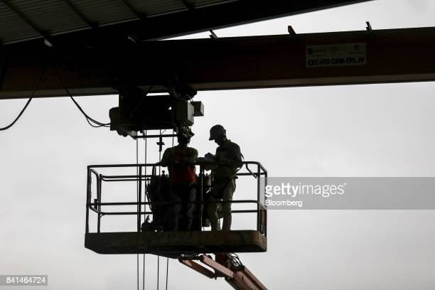 Workers are silhouetted as they work on an elevated platform at the Mumbai Metro Rail Corp casting yard in Mumbai India on Monday Aug 28 2017 The...
