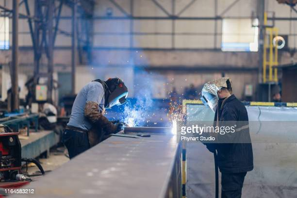 workers are welding  part in factory - manufacturing stock pictures, royalty-free photos & images