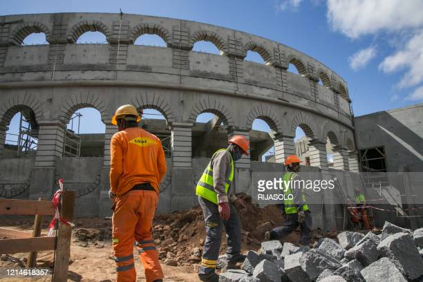 Workers are working on the construction site of a concrete arena on the historic site of the Queen's Palace in Antananarivo on May 22, 2020.