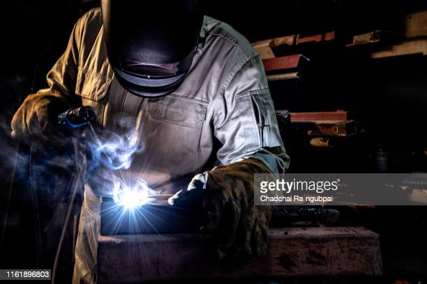 workers are working to weld steel with electric welding systems and put masks and protective clothing for factory safety. - fabricage apparatuur stock pictures, royalty-free photos & images
