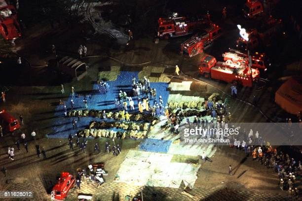 Workers arrange bodies of the victims as the rescue operation continues after the China Airlines Flight 140 crashed at Nagoya Airport on April 26...