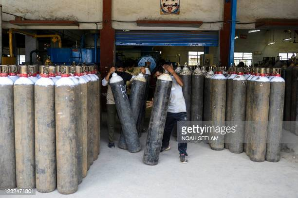 Workers arrange medical oxygen cylinders to transport to hospitals for the Covid-19 coronavirus treatment in a facility on the outskirts of Hyderabad...
