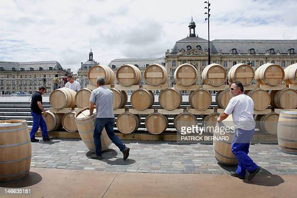 Workers arrange wine barrels on a dock of the French southwestern city of Bordeaux on June 21 to prepare the setting of the 'Fete du vin' running...