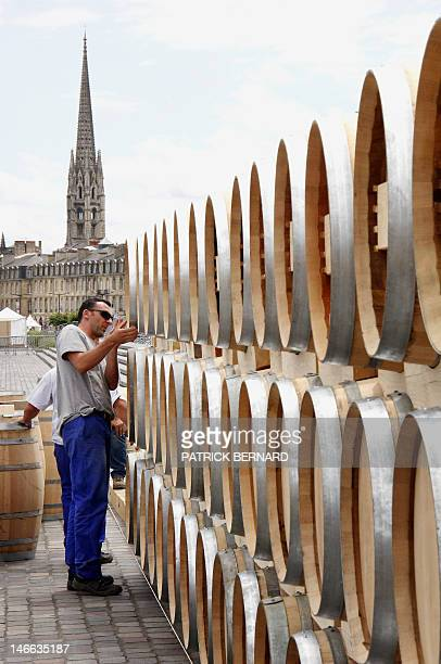 Workers arrange wine barrels on a dock of the French southwestern city of Bordeaux on June 21 to prepare the setting of the Fete du vin running from...