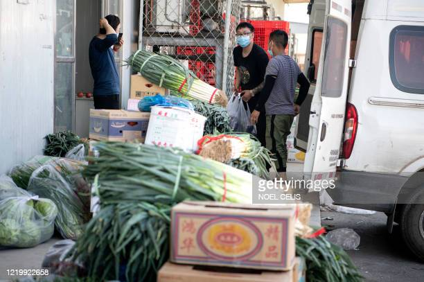 Workers arranges vegetables at the closed Xinfadi Market in Beijing on June 14 2020 The domestic COVID19 coronavirus outbreak in China had been...