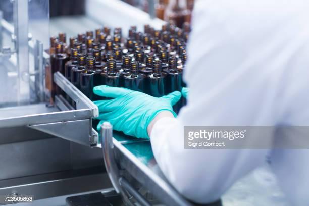workers arranging bottles on conveyor belt on production line in pharmaceutical plant, mid section - sigrid gombert stockfoto's en -beelden