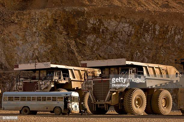 Workers arrive in front of mining trucks at the AngloGold Ashanti Ltd Cripple Creek Victor gold mine in Victor/Cripple Creek Colorado US on Thursday...