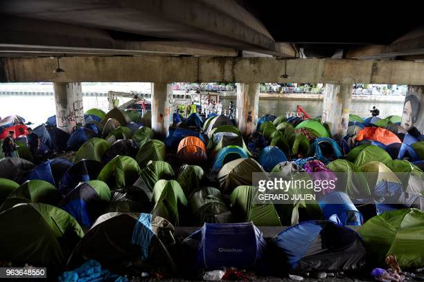 TOPSHOT Workers arrive to clean up the Millenaire migrants makeshift camp along the Canal de SaintDenis near Porte de la Villette northern Paris...